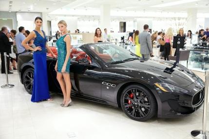 Model posing next to luxury car from O'Gara Coach Westlake