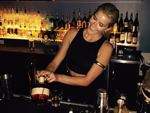 Behind the bar, Kate Havness pours her favorite whisky, Blanton's (photo by Scott Bridges)